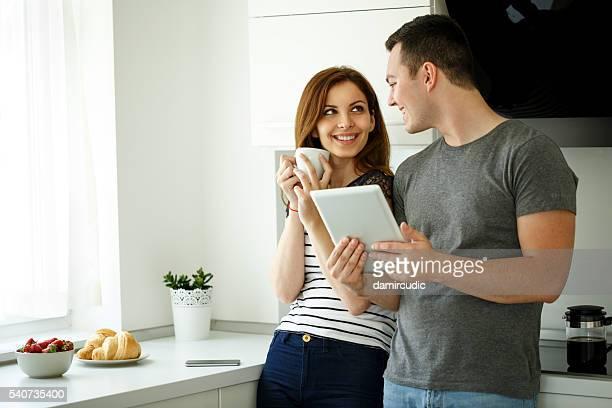 Attraktives Paar mit Digitaltablett im der Küche