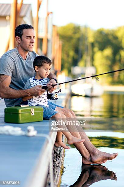Attractive dad teaching his young boy how to fish
