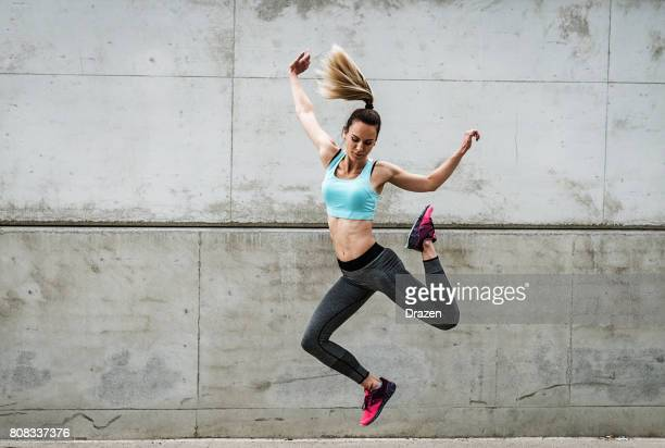 attractive dancer exercising and jumping near the concrete wall - sportsperson stock pictures, royalty-free photos & images