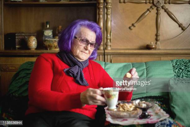 attractive elderly woman with cup of coffee - purple hair stock pictures, royalty-free photos & images