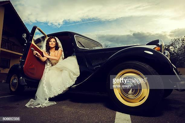 attractive elegant bride in old car