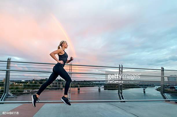 Attractive female athlete sprinting across a bridge
