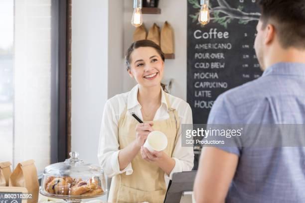 Attractive female barista takes male customer's order