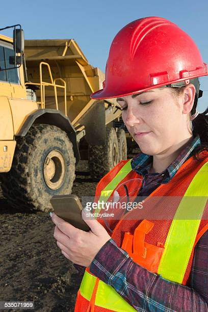 Attractive Female Construction Worker and Construction Site with Smartphone Texting