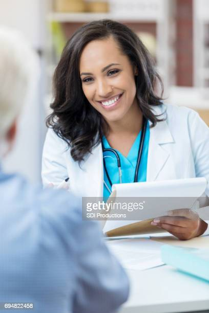 attractive female doctor discusses something with colleage - health insurance stock pictures, royalty-free photos & images