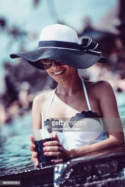 attractive female drinking cocktail in pool during vacation - aleksandar georgiev stock photos and pictures