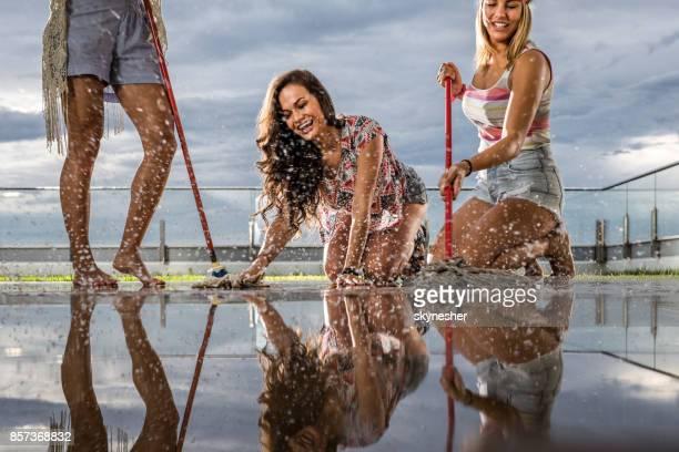 Attraktive Freundinnen feuchte Bodenreinigung auf einen Balkon.
