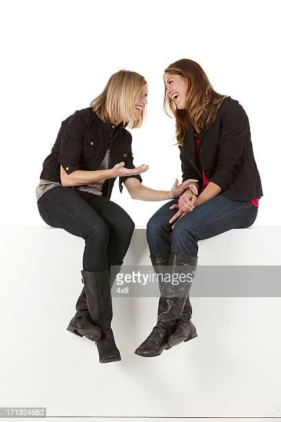 Attractive female friends sitting on the ledge of a wall