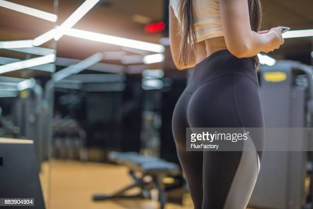 attractive female in a gym in a hot pants - woman bum stock photos and pictures