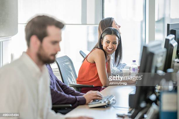 attractive female office worker using computer, laughing - work romance stock pictures, royalty-free photos & images