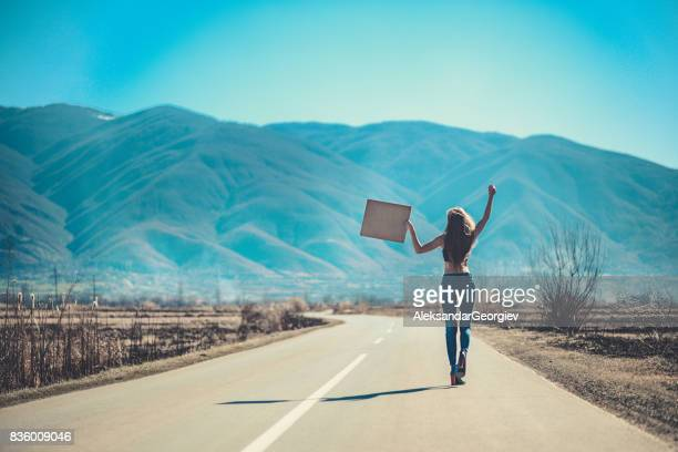 Attractive Female on Empty Road Hitchhiking with Raised Blank Sign Board