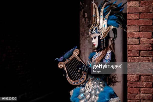 attraktive frau posiert in venedig karnevalskostüm - masked musicians stock-fotos und bilder