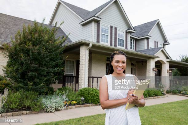 attractive female realtor checks home for sale - real estate agent stock pictures, royalty-free photos & images