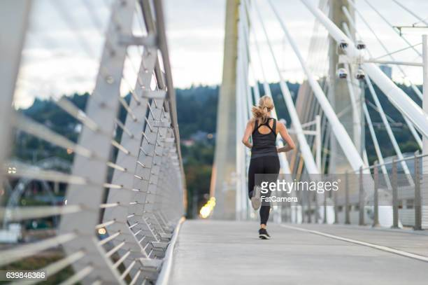 Attractive female running in the city across a pedestrian bridge