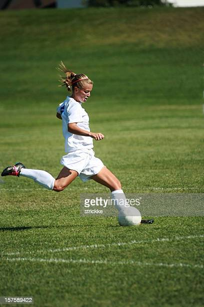 Attractive Female Soccer Player in Profile Kick with copyspace