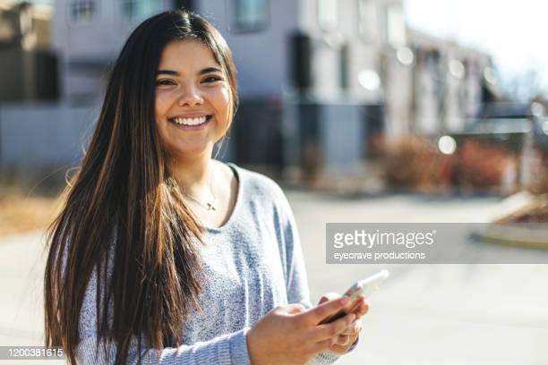スマートフォンを使ったヒスパニック系エスニシティの魅力的なジェネレーションz若い女性 - ネイティブアメリカン ストックフォトと画像