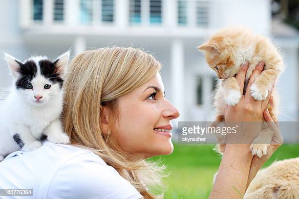 Attractive girl enjoys outdoor with cats.