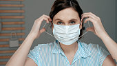 Attractive girl puts on surgical mask on her face. Cold, flu, virus, acute respiratory infections, quarantine, epidemic, irony, sarcasm concept. Close up