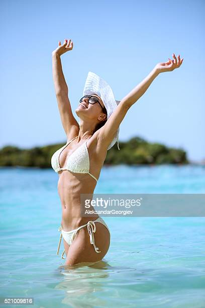 Attractive Girl Sunbathing in Sea with Arms Raised to Sky