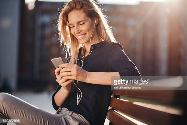 Attractive girl with headphones embracing the sunny day
