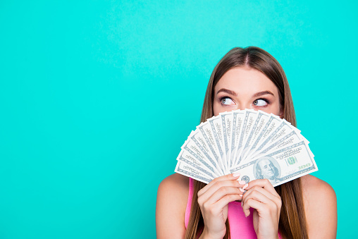 Attractive gorgeous young amazed girl wearing pink blouse, excited, covering face with dollar banknotes. Copy space. Isolated over bright vivid blue teal, turquoise background 1055961984