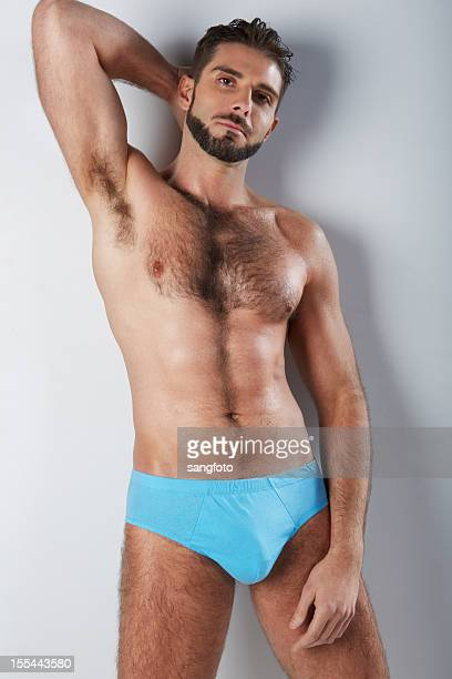 attractive hairy man in blue underwear arm behind head - hairy chest stock photos and pictures