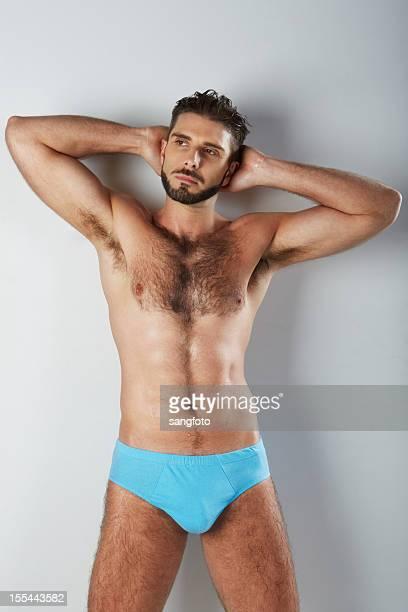 attraktive behaart mann in blauen unterwäsche arme hinter dem kopf - hairy chest stock-fotos und bilder