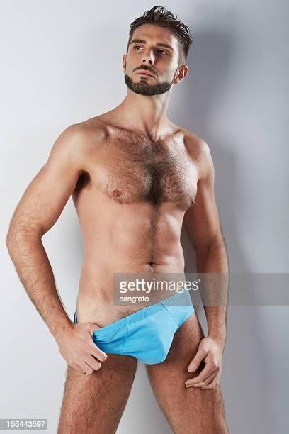 attraktive behaart mann in blauen unterwäsche hand an der hüfte - behaart stock-fotos und bilder