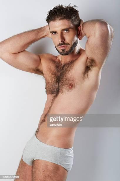 attraktive behaart mann in grau unterwäsche die arme hinter dem kopf - behaart stock-fotos und bilder