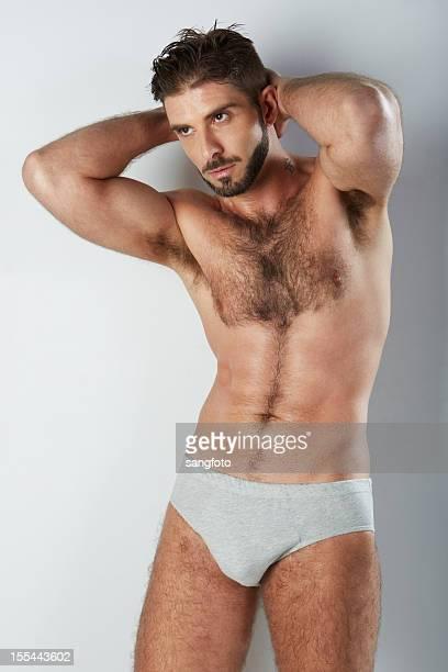 attraktive behaart mann in grau unterwäsche die arme hinter dem kopf - hairy chest stock-fotos und bilder