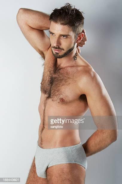 Attractive hairy man in grey underwear hand behind back