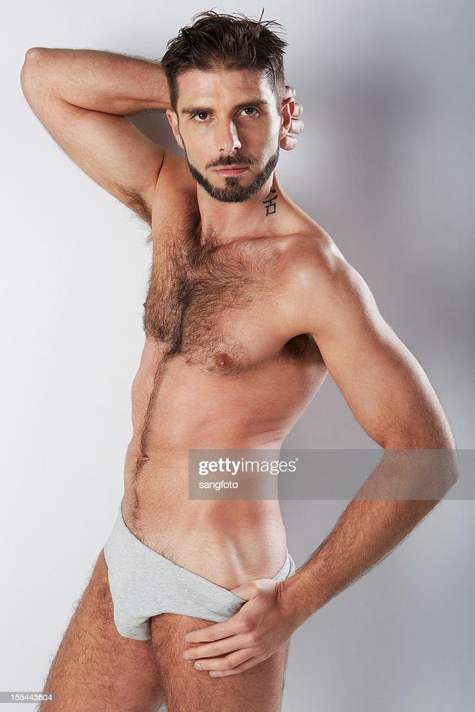 Attractive hairy man in grey underwear hand on hip : Stock Photo