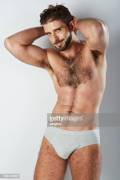 attractive hairy man in grey underwear smirking - hairy chest stock photos and pictures