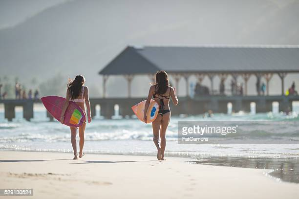 Attractive hawaiian female surfers at the beach