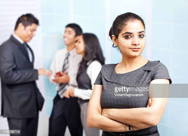 Attractive Indian Businesswoman with colleagues in the background