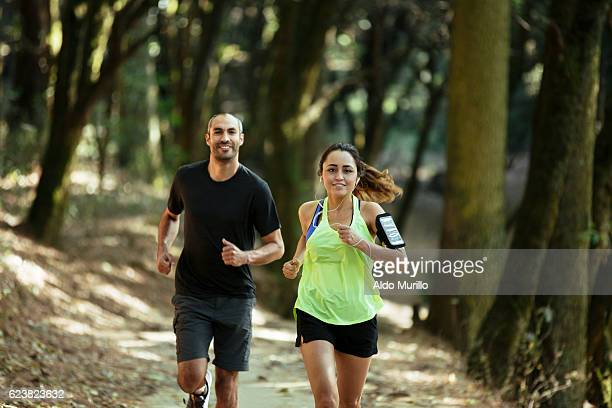 Attractive latin couple running and looking at camera