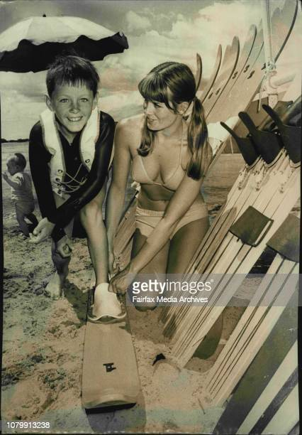 Attractive Lindy Hall of Bayview helps 9 year water skiing enthusiast Ken Clifford of Newport adjust his skiis ***** spin across Narrabeen Lakes Ken...