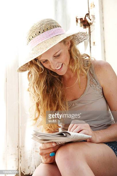Attractive long-haired blonde woman doing crossword