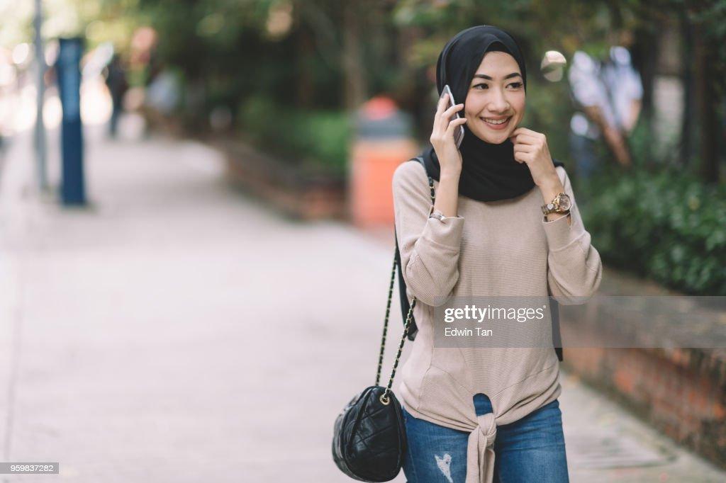 attraktive malaiischen Dame mit Kopftuch auf die Telefon-Kommunikation : Stock-Foto