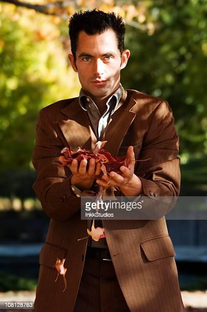 魅力的な男性の保持秋の葉とカメラ目線