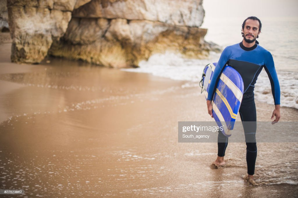 Attractive man carrying surfboard at the beach : Stock Photo