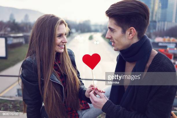 attractive man giving red paper heart to his girlfriend - love you stock photos and pictures