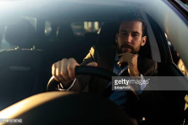 homme attirant dans la voiture de conduite de costume d'affaires - un seul homme photos et images de collection