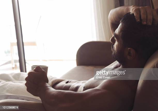 Attractive Man in towel getting away from it all from the hotel room and drinking coffee - Luxury Hotel Concept