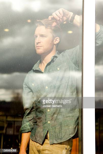 Attractive man looking out a window.