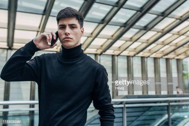 携帯電話で話す魅力的な男 - タートルネック ストックフォトと画像