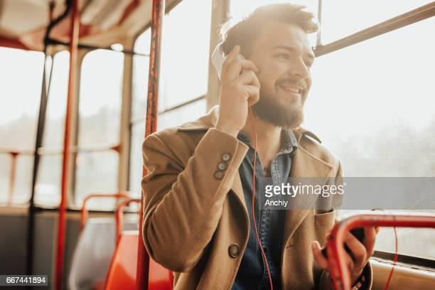 Attraktiver Mann am Telefon zu sprechen, im öffentlichen bus