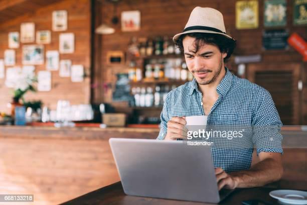 Homme séduisant à l'aide d'un ordinateur portable au café