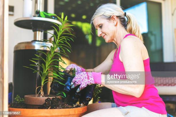 Attractive mature Adult Female Potting Plants and Flowers During Spring Garden Planting Season