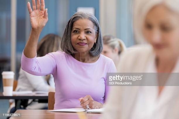 attractive mature african american woman raises hand in class - adult stock pictures, royalty-free photos & images